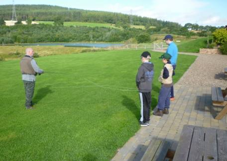 Coach Steve McCann showing youngsters the correct method of casting before heading down to the water