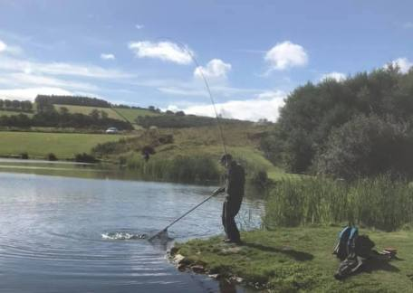 Alec Close netting a fish on Long Crag
