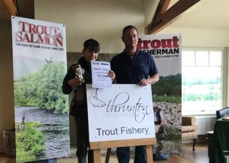 Charlie Southworth with his prize for the best fish, presented by Anthony Meadows