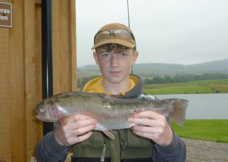 Thrunton Junior Jay McEwan delighted with this 3lb rainbow after a lesson with Barry Mtchell