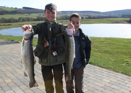 Harrison Douds with 2 of his fish he landed on a diawl bach watched by his younger brother
