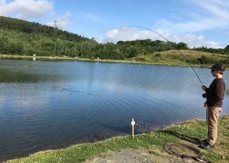 Max Mockridge fishing for Clatworthy Fishery into a fish.