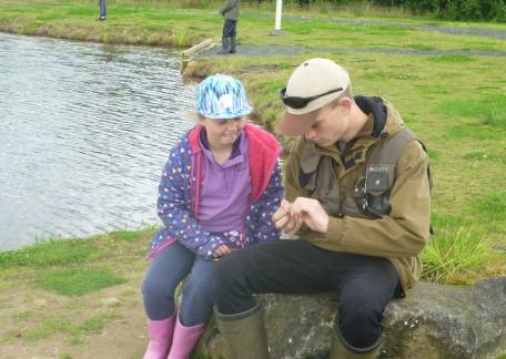 Joe helping one of the new starters tie another fly on her line