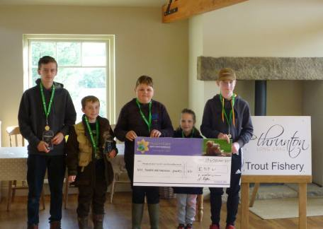 The Thrunton Juniors who competed in the charity fundraiser holding the cheque before presenting it to Rebecca from the Hospice