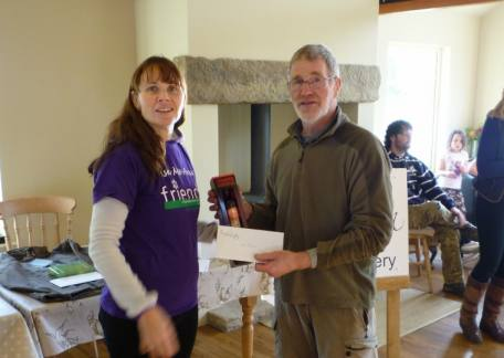 Dick Taylor , winner of the charity fundraiser being presented his prize by Rebecca from the North Northumberland Hospice