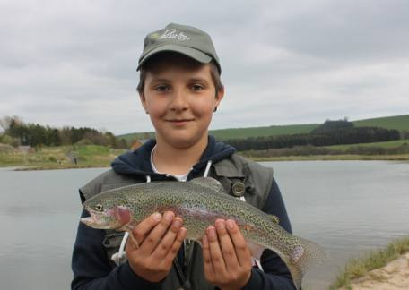 Junior angler Shaun Silk with his first fish during a coaching session at Thrunton