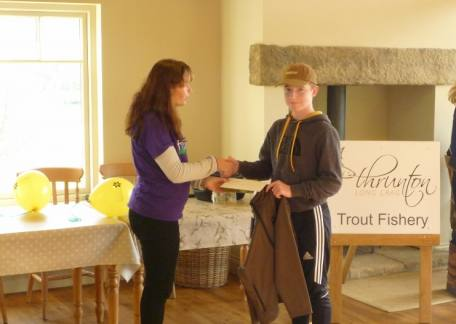 Jay McEwan receiving his first prize from Rebecca Taylor from the North Northumberland Hospice